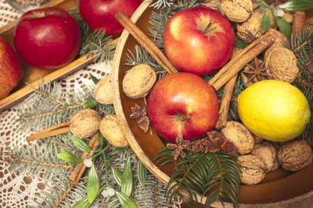 Xmas basket with apple, vlanuts, needles and cinnamon photo