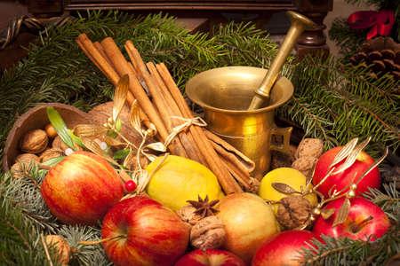 Xmas basket with apple, vlanuts, needles and mortar photo