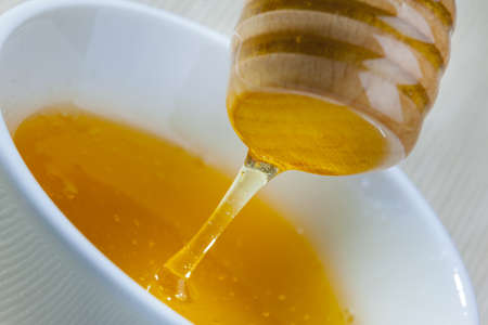ceramic bowl with honey and a wooden spoon