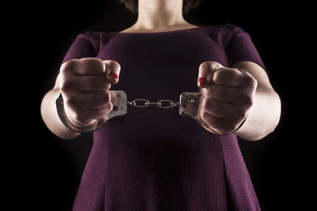 submissive woman wearing a purple dress in metal handcuffs on black background Stock Photo