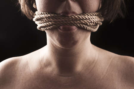 submissive girl gagged with rope on a black background Stockfoto