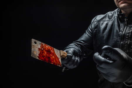 Serial killer's hand with bloody meat cutter and black gloves