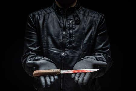 Serienmörder-Maniac, der mit Handschuhen / Killerwerkzeugen Messer an den Händen hält