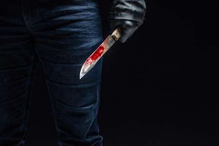 La main du tueur en série avec un couteau sanglant et des gants noirs