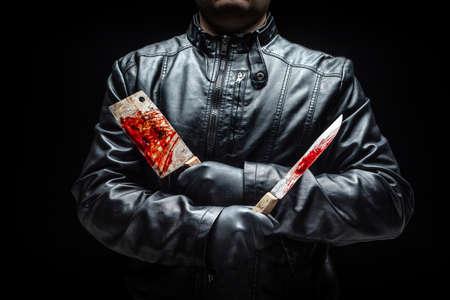 Serienmörderhand mit blutigen Killerwerkzeugen und schwarzen Handschuhen Standard-Bild