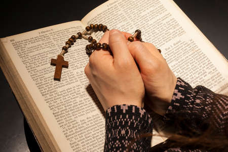 Hands of young woman with holy bible and rosary