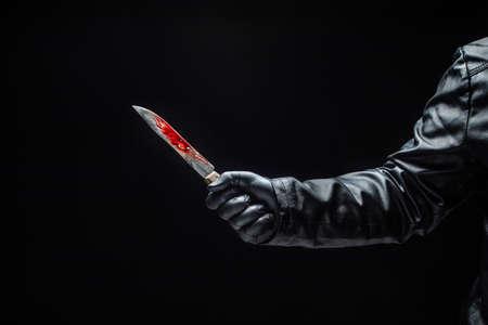 Hand eines Serienmörders mit blutigem Messer