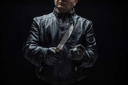 Serial killer maniac with knife and black gloves