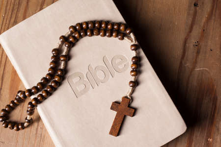 Holy Bible with rosary  on wooden table