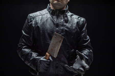 Serial killer maniac with meat cutter and black gloves