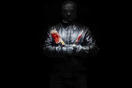 Serienmörderhand mit blutigen Killerwerkzeugen und schwarzen Handschuhen