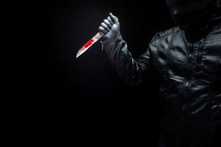 Serial killers hand with bloody knife and black gloves