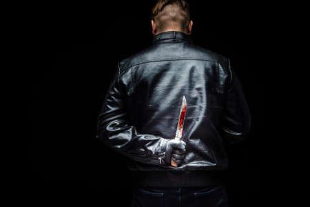 Serial killer maniac holding killer tools behind his back Фото со стока