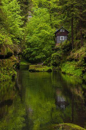 Beautiful hut among the trees reflecting in the river Kamenice, National Park Bohemian Switzerland (Ceske Svycarsko), Czech Republic