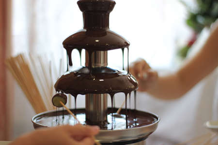 Childrens hands hold fruit on a stick under the dripping chocolate in a chocolate fountain Stock fotó