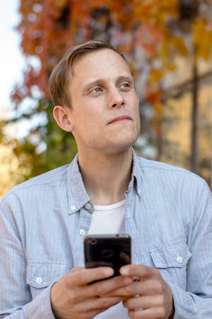 Portrait of guy with a phone in casual clothes, a successful student in blue shirt is enjoying life Imagens