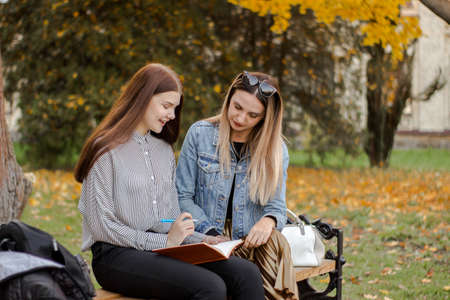 Two girlfriends take notes while sitting on a bench in autumn park. Sisters look in an orange notebook. The elder carefully teaches the younger