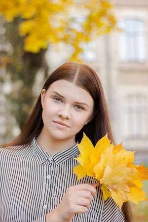 Portrrait of atmospheric lifestyle photo of a smiling beautiful girl. Brown-haired lady holds in her hand yellow leaves. Sunny autumn concept