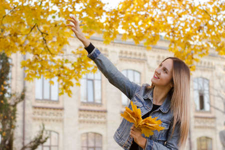 Warm lifestyle colorful photo of a cute woman. Lady holds in her hand yellow leaves. Sunny autumn concept