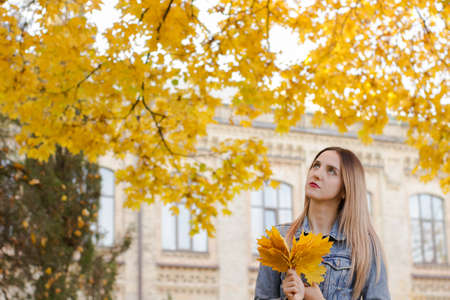 Warm lifestyle photo of a cute woman. Lady holds in her hand yellow leaves. Sunny autumn concept