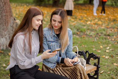 Two beautiful young girls are looking into the phone, sitting on a bench in the autumn park. Sisters communicate online in social networks on a smartphone. The eldest carefully listens to the younger