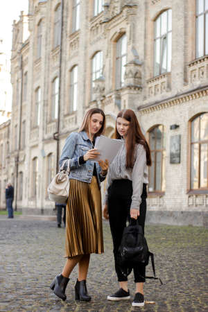 Two beautiful young friends stand near the university and look at the paper. Sisters are studying the contract for admission. Elder carefully explains younger test results