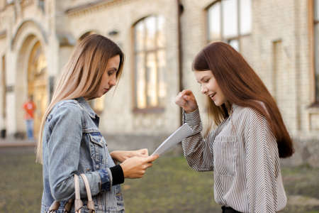 Two girlfriends stand near the university and look at the papers. Sisters are studying the contract for admission Фото со стока