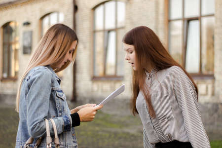 Two attractive young girlfriends stand near the university and look at the papers. Sisters are studying the contract for admission. Elder carefully explains younger test results Banco de Imagens