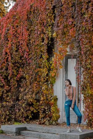 Young cute girl in multi-colored suspenders. Young student in autumn park