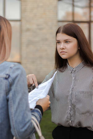 Unhappy girl is standing near the university and points to paper. Sisters are studying the contract for admission. Elder carefully explains younger test results