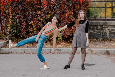Two beautiful students walking in the autumn park. Girls have fun outdoor