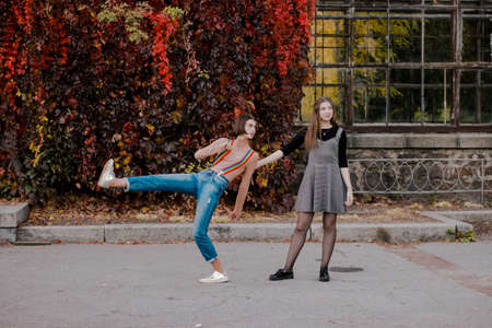 Students walking in the autumn park. Girls have fun outdoor