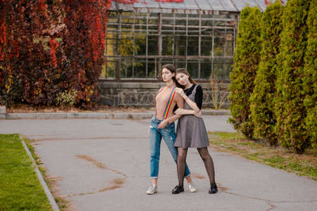 The girl hugs his girlfriend tightly. Students in the autumn park. Young women are dreaming in nature Banque d'images