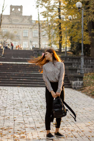 Girl with a backpack stands near the steps leading to the university. Young woman in autumn park. Concept of learning
