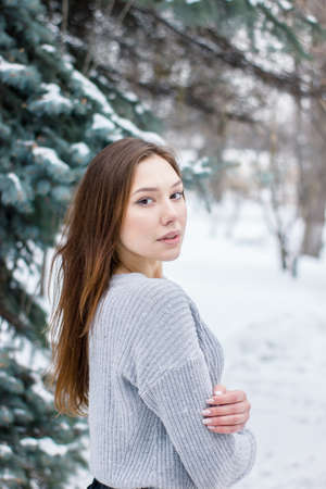 Pretty young woman looking into the frame in snowy weather. The girl holds her hand. Winter concept Imagens