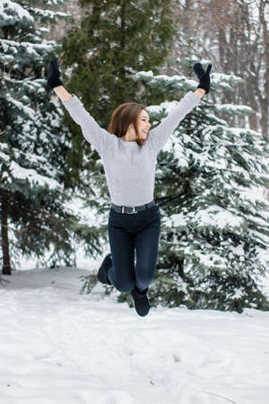 Girl in mittens on the background of snowy Christmas trees. Pretty young woman jumping enjoying the snowy weather. Winter concept Imagens