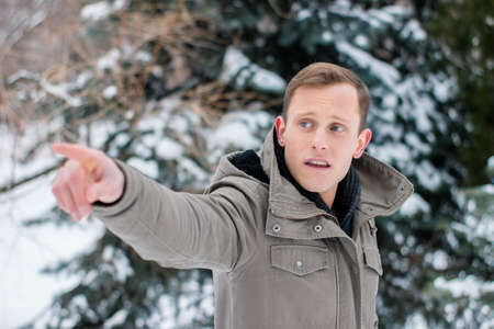 A young man in a winter landscape indicates the direction of his right hand. The guy points to the right. Conceptual winter photo with space for text Imagens
