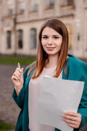 A woman holds securities and a pen in her hands, standing next to the university. Business lady offers to sign a contract Imagens