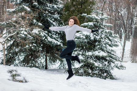 Pretty young woman jumping enjoying the snowy weather. Girl in mittens on the background of snowy Christmas trees. Winter concept