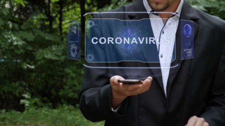 Unrecognizable businessman activates conceptual HUD holograms on smartphone with text Coronavirus. Bearded man in a white shirt and a jacket with a holographic screen on a background of green trees