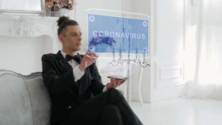 Guy businessman activates conceptual HUD hologram on smartphone with text Coronavirus. Young man in a white shirt and a jacket with a holographic screen on a background of the luxury room