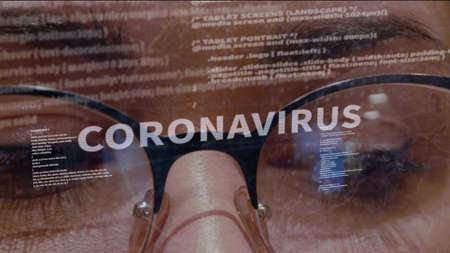 Coronavirus text on the background of female software developer. Eyes of woman with glasses are looking at programming network code space abstract technologies connecting global data network Imagens