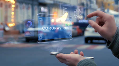 Female hands on the street interact with a HUD hologram with text Coronavirus. Woman uses the holographic technology of the future in the smartphone screen on the background of the evening city