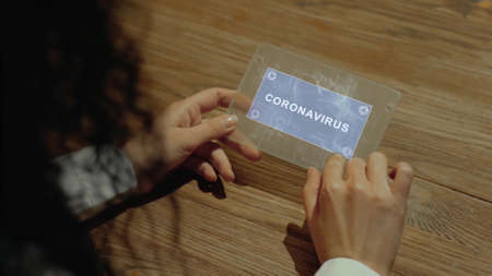 Unrecognizable woman working on a futuristic tablet with a hologram text Coronavirus. Womens hands with future holographic technology at a wooden table
