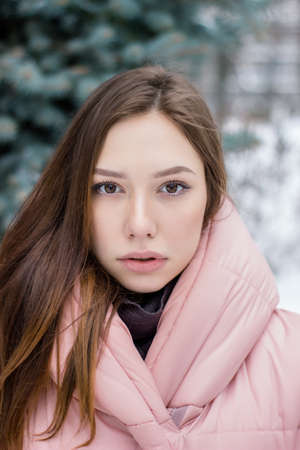 Pretty young woman looking into the frame in snowy weather. The girl on the background of the Christmas tree. Winter concept copy space Imagens