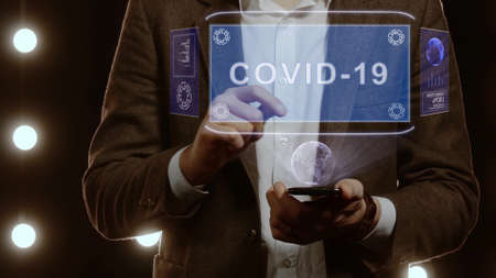 Businessman activates conceptual HUD hologram on smartphone with text COVID-19. Man in a white shirt and jacket with a holographic screen on the background of lights