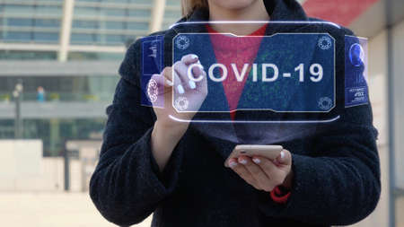 Unrecognizable woman interacts HUD hologram with text COVID-19. Girl in the coat uses the technology of the future mobile screen on the background of the city Imagens
