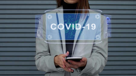 Unrecognizable business woman, interacts with a HUD hologram with text COVID-19. Girl in a business suit uses the technology of the future mobile screen against the background of a striped wall Imagens
