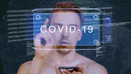 Young man interacts with a conceptual HUD hologram with text COVID-19. Guy with future technology mobile screen on background of the program code Stock Photo