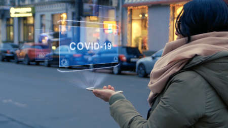 Unrecognizable woman standing on the street interacts HUD hologram with text COVID-19. Girl in warm clothes with a scarf uses technology of the future mobile screen on background of night city Imagens